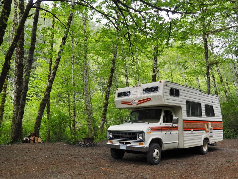 Recreational Vehicle Camping in Lush Green Forest. Motor home parked at campsite in the forest stock photos