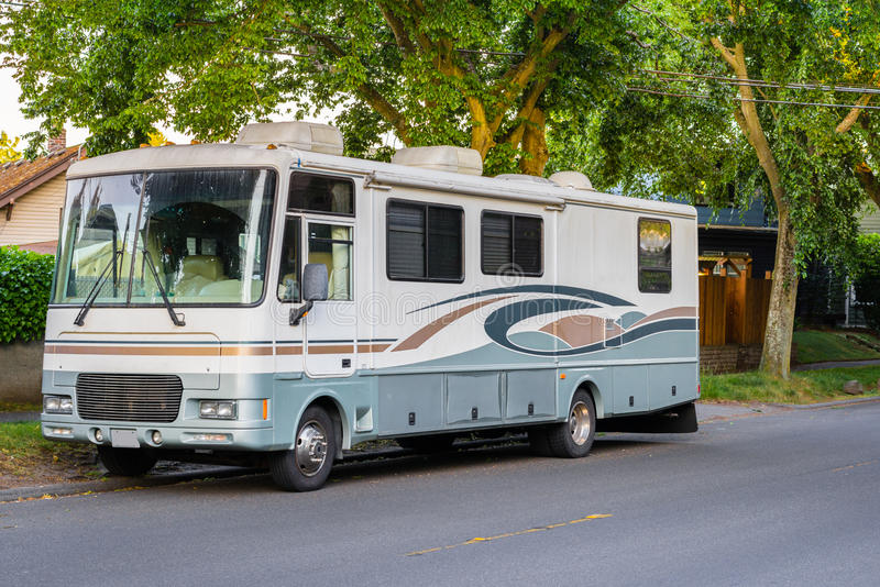 Recreational vehicle parked. Weathered recreational vehicle parked on the side of the street stock photos