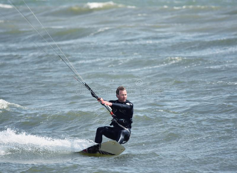 Recreational Water Sports Action. A Kiteboarder riding the waves. Dorset, UK. May 2018. royalty free stock images