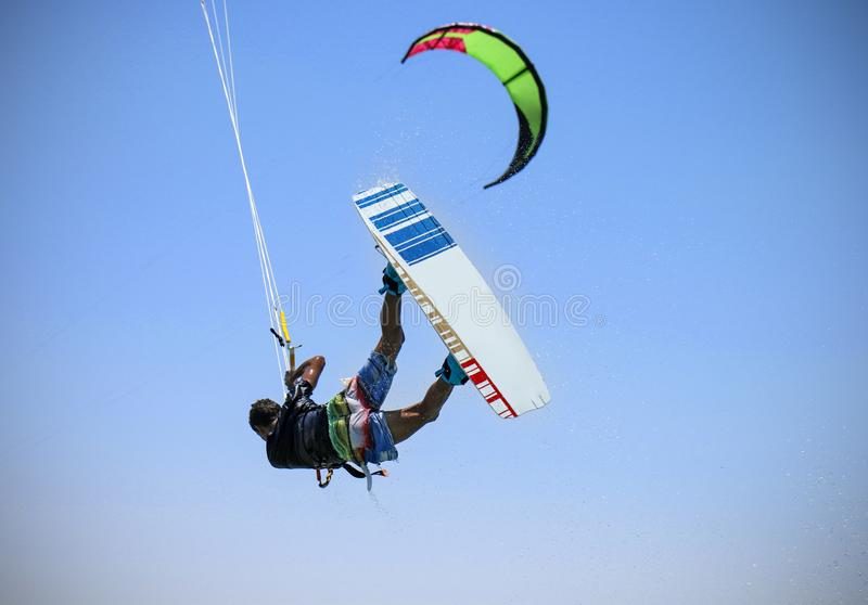 Recreational water sports: kitesurfing. Kiteboarding sportsman jumping high in the sky on windy day. Extreme sports action. With wind and water. Healthy active royalty free stock photography