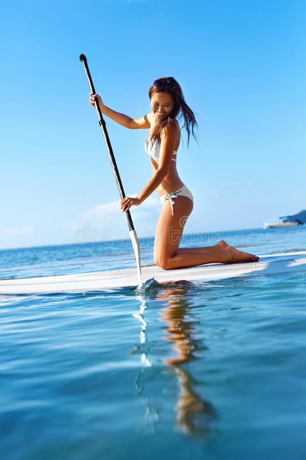 Free Recreational Water Sports. Woman Paddling On Surf Board. Summer Royalty Free Stock Photos - 66820418