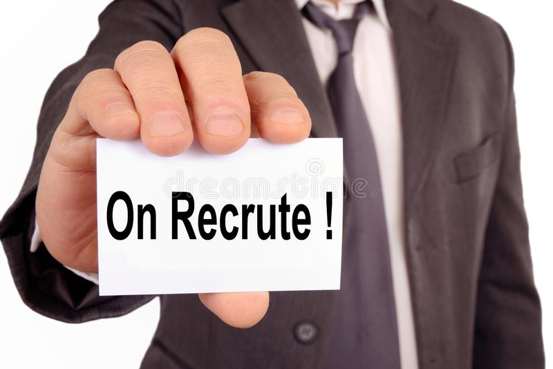 We recruit written in French. Unrecognizable man holding a card on which is written in French we recruit stock photography