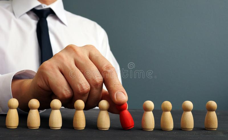 Recruiter choosing one figurine from the crowd. Talent management and hiring. Concept royalty free stock photo