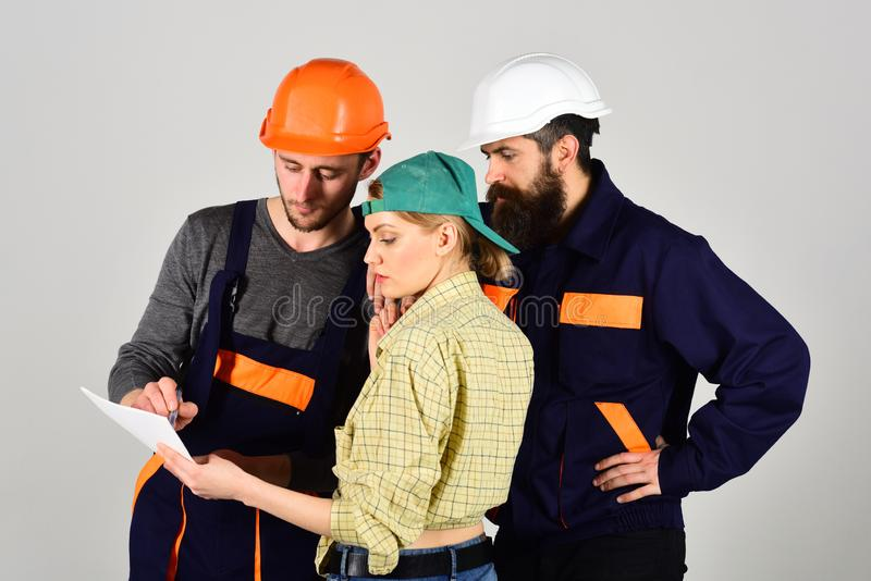 Recruitment concept. Brigade of workers, builders in helmets, repairers and lady discussing contract, grey background stock photo