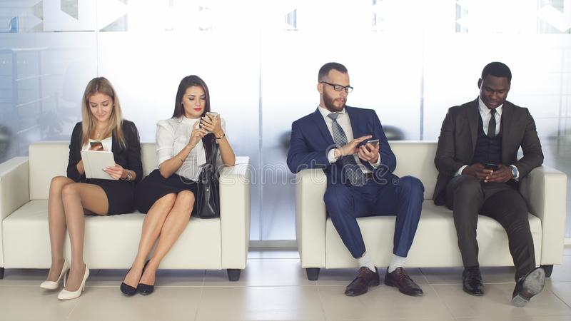 Recruitment to the company. Young applicants are awaiting interview. a group of young people bored waiting for job royalty free stock photography