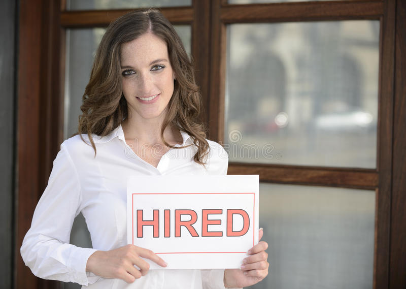 Recruitment : woman holding a hired sign. Recruitment : happy woman holding a hired sign stock image