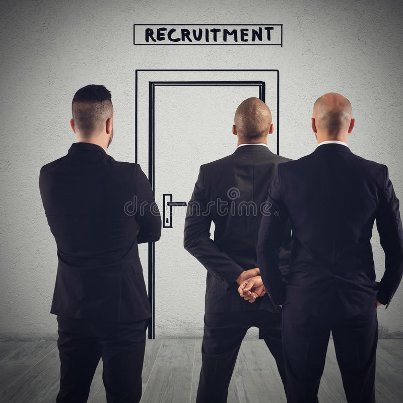 Recruitment for a workplace. Businessmen are waiting in front of the door of recruitment as candidates to the workplace stock photo
