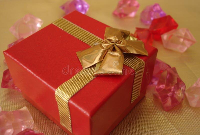 Rectángulo de regalo rojo en un fondo de oro hermoso fotos de archivo