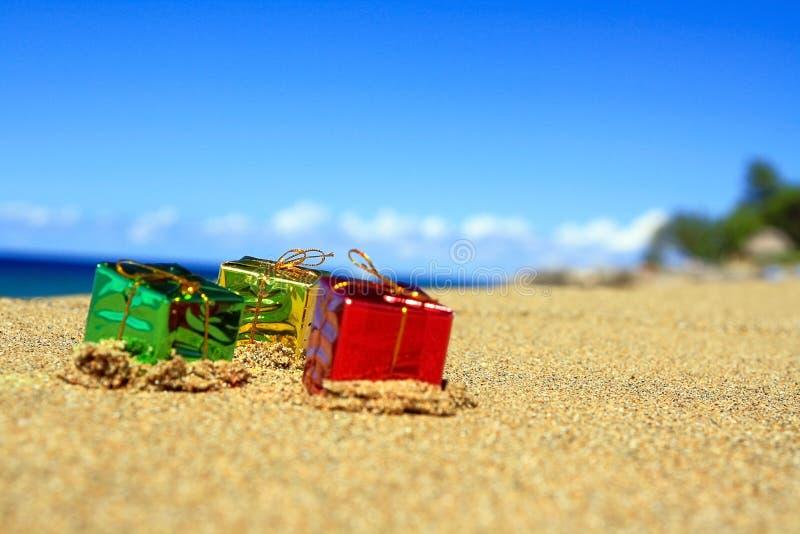 Rectángulos de regalo del color de Trhee en la playa del océano imagenes de archivo