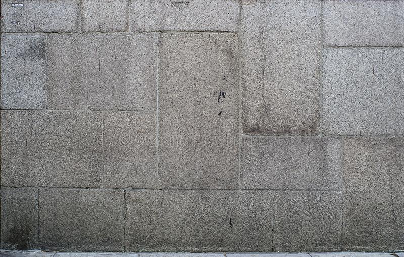 Rectangle brown granite mounted on facade. Dirty and old stone tiles protect wall from bad weather. Also that granite gives the facade a massive and unshakable royalty free stock images