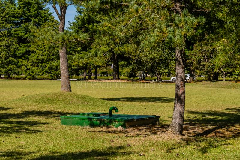 Rectangle maintenance access in park. Green, rectangle underground maintenance access point shaded by evergreen trees in public park on sunny afternoon royalty free stock photos