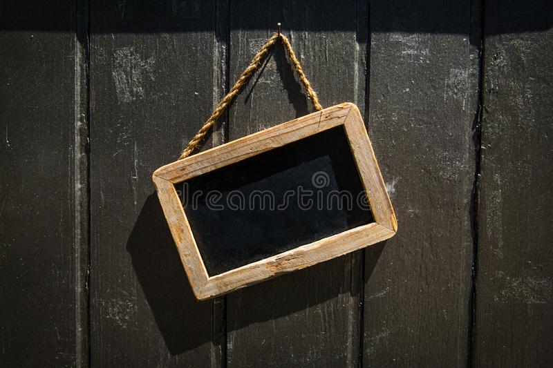Rectangular Blackboard Shop Sign with Wooden Frame on a Wood Wall. stock images