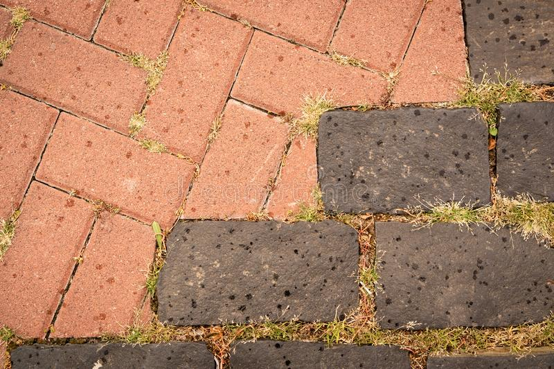 Rectangular ceramic tiles of terracotta and gray with bunches of green grass in sections. stock photos