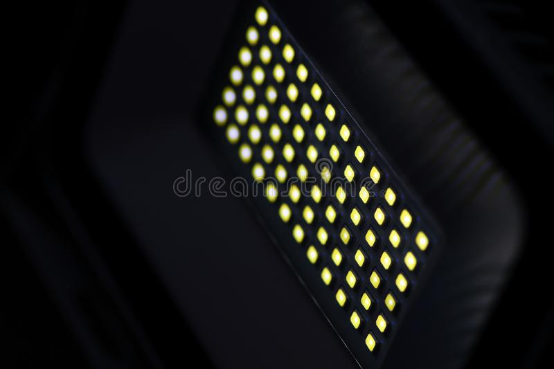 A rectangular diode spotlight of gray color in a dark room illuminates with yellow light. royalty free stock photo