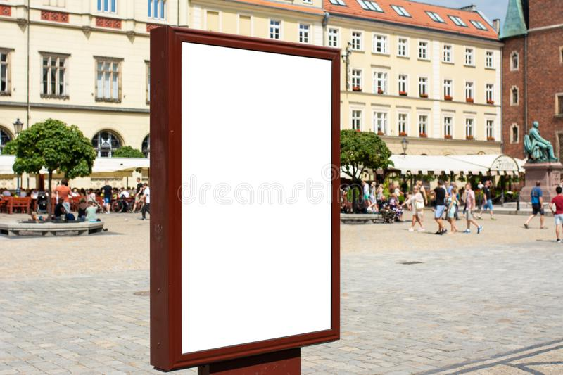 Rectangular White Mockup Poster City Advertisement Isolated On The Street. Blurred background with old center building and walking people stock images