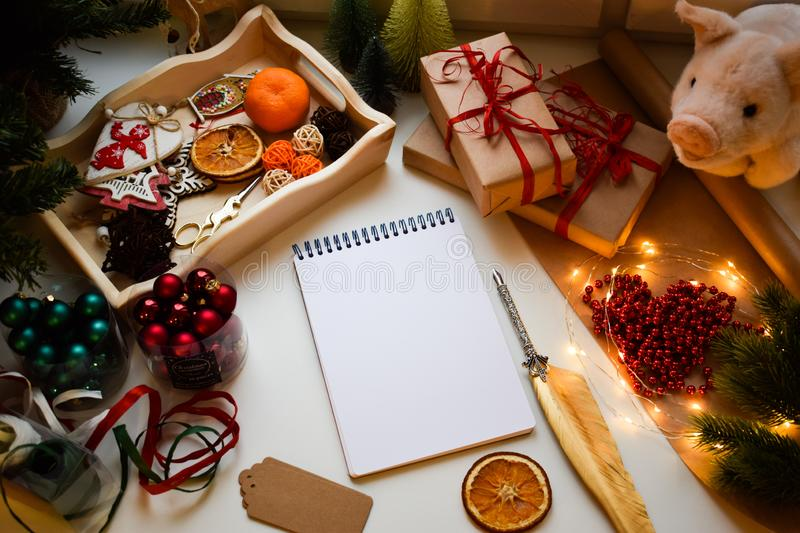 A rectangular white notebook on a white background surrounded by pigs and Christmas and New Year trifles stock images