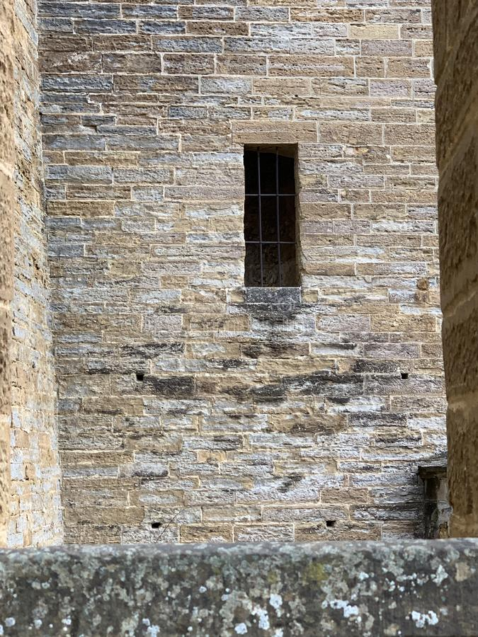 A rectangular window on a stone wall of Hohenzollern castle with a metal bars grid on it royalty free stock photo