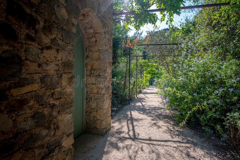 Rectilinear footpath and stone building in a Mediterranean garden stock image