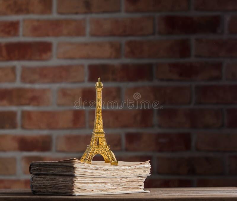Recuerdo de oro de la torre Eiffel y libros viejos imagen de archivo