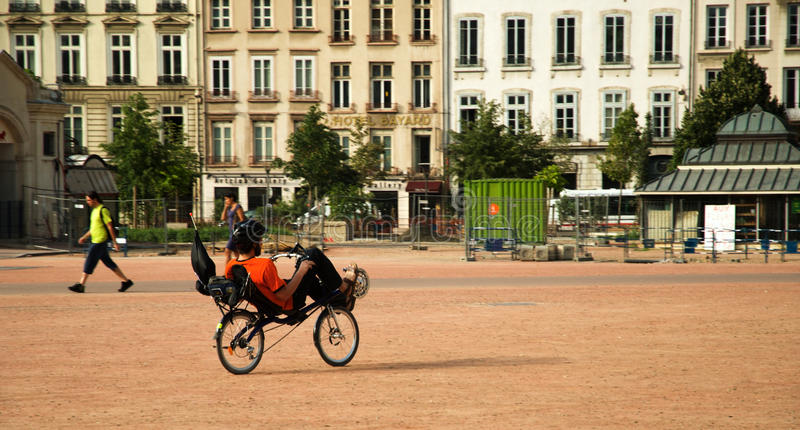 Recumbent bicycle. Rider on the square in Lyon stock image