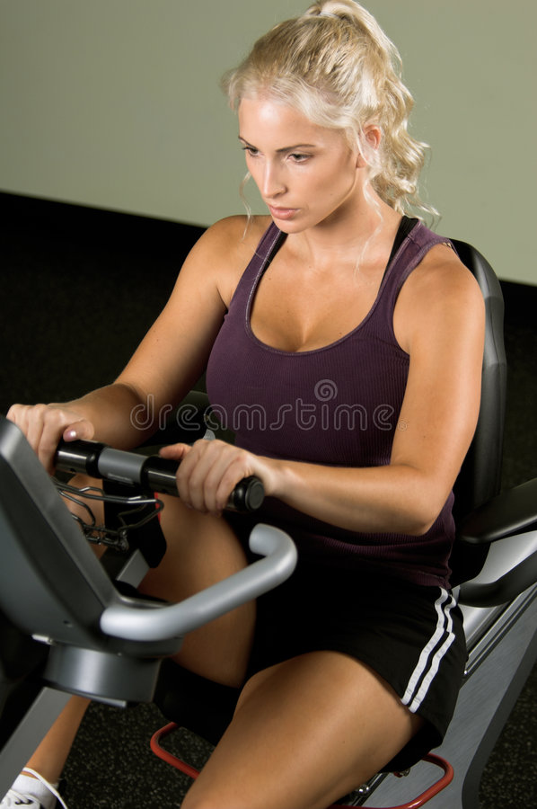 Recumbent Exercise Bike. Beautiful blond woman during a cardio workout on a recumbent exercise bike in the gym royalty free stock photo