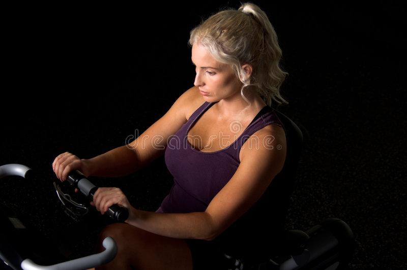 Recumbent Exercise Bike. Beautiful blond woman during a cardio workout on a recumbent exercise bike in the gym royalty free stock photos