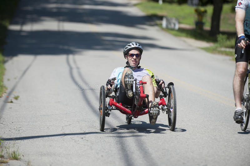 Recumbent tricycle rider. DIGHTON, MASSACHUSETTS, AUGUST 7, 2010: Rider on a recumbent tricycle enjoys a short downhill in Pan-Mass Challenge charity ride for stock photos