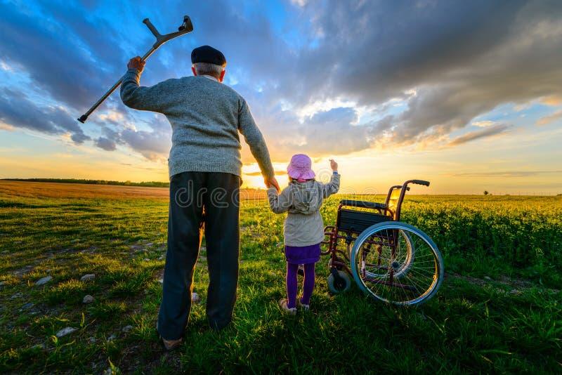 Recuperação do milagre: O ancião levanta-se da cadeira de rodas e levanta-se as mãos acima imagem de stock