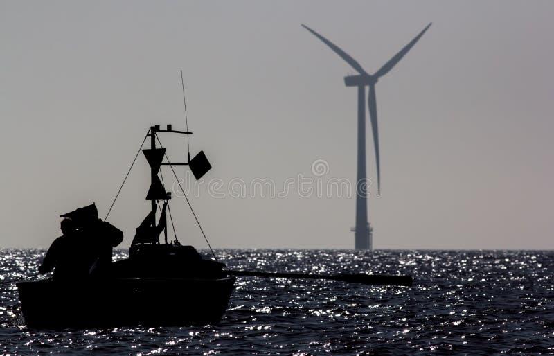 Recursos sustentáveis Barco de pesca pequeno na frente dos wi a pouca distância do mar imagens de stock