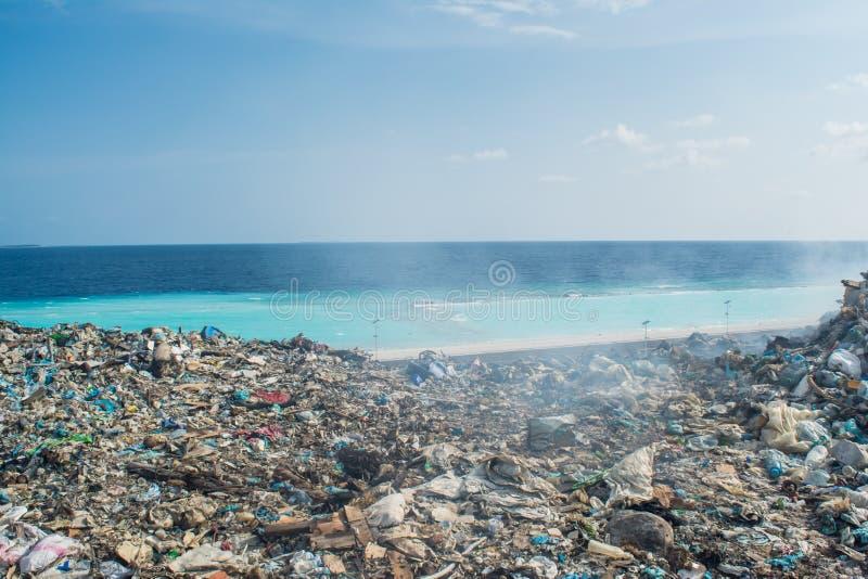 Recuse na descarga de lixo perto da praia completamente do fumo, da maca, de garrafas plásticas, de desperdícios e de lixo na ilh imagens de stock