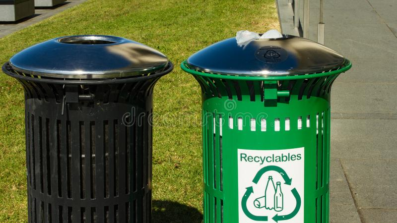 Recyclable bin and a trash bin side by side. On a sunny day royalty free stock photos