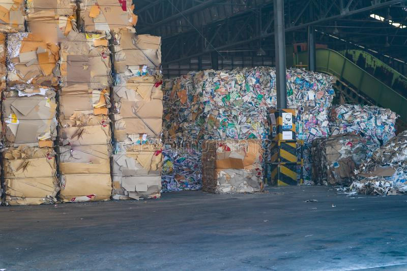 The recycle industry cardboard garbage and paper waste after pressing in hydraulic baling garbage press machine to a square dense stock image