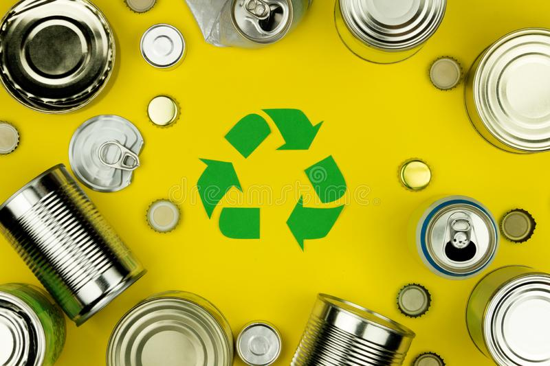 Recycle reuse sign symbol with metal aluminium cans, covers, jars. Green recycle reuse sign symbol with metal aluminium cans, covers, jars on yellow background royalty free stock photo