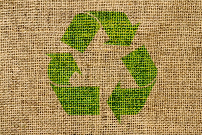 Recycle symbol on hessian. Close up of hessian textured background with reycycling symbol stock image