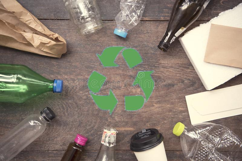 Recycle symbol and plastic, paper, glass on wood table. Background top view. eco and save the earth concept royalty free stock photography