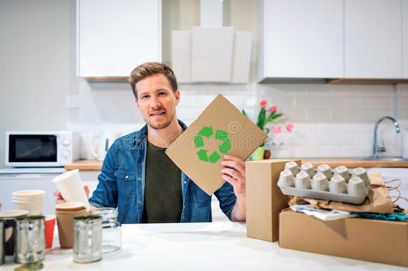 Recycle symbol. Young responsible man holding cardboard with recycle icon while sitting at the table with other waste at. Recycle symbol. Young responsible man royalty free stock photos