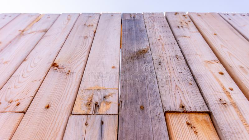 Recycled wood fence made from salvage wood beams disassembled from mattress frames or palette wood, as an example of a zero-waste stock photos