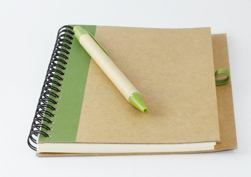 Recycleer notitieboekje en een pen stock afbeeldingen
