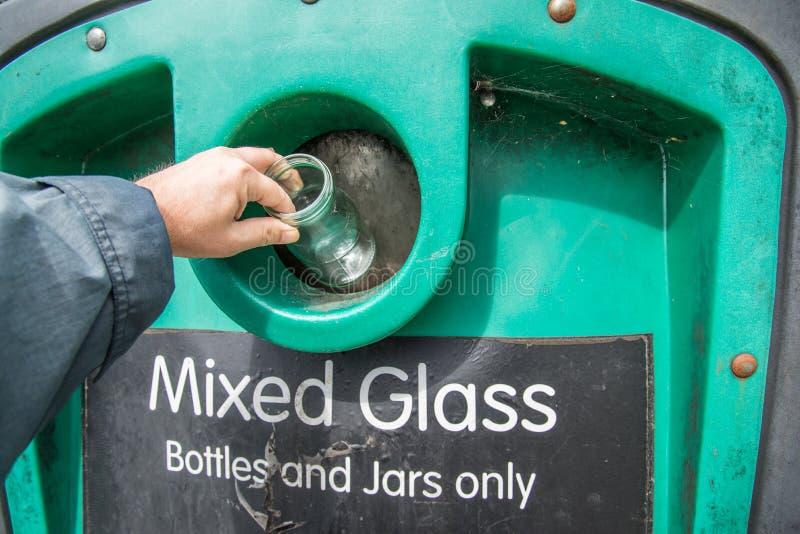 Recyclerende bak, man wapen die glaskruik zetten in kringloopbak bij flessenbank in U K stock foto's