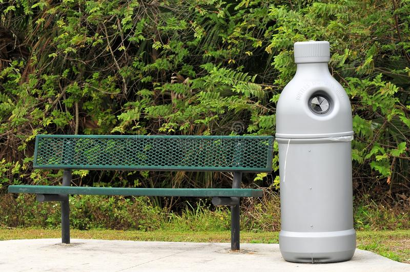 Recycling. Green metal bench and silver grey recycling bin for bottles and cans in a South Florida nature friendly park royalty free stock photos