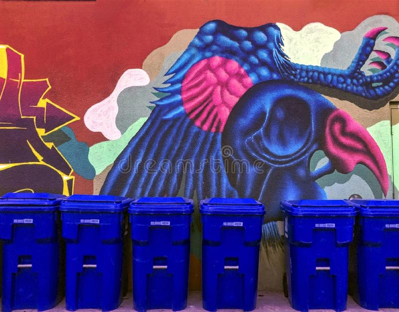 Recycling blue bins lined up against colorful wall mural of big blue creature stock images
