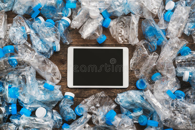 Recycling concept. Tablet wooden background around the transparent plastic bottles. The problem of ecology, environmental pollutio royalty free stock photo