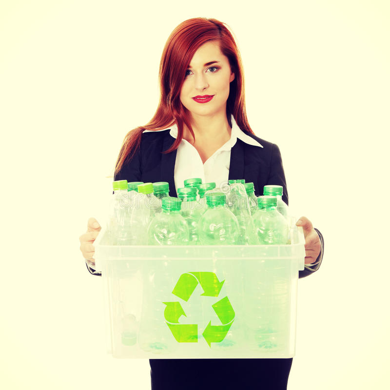 Recycling concept. Young businesswoman carrying a plastic container full with empty recyclable household material. Recycling concept royalty free stock photography