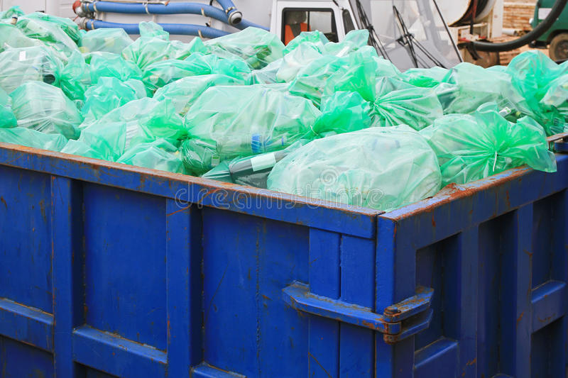 Recycling dumpster. Dumpster container with green bags for recycling royalty free stock images