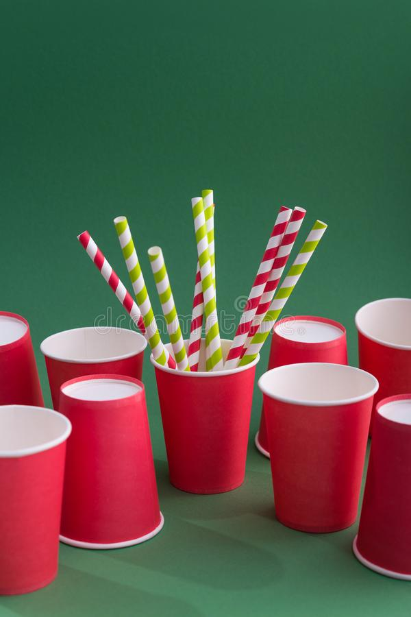 Recycling eco concept. pop art style. Bright red colored cocktail straw in paper cup on a color green background. recycling eco concept. pop art style stock photo
