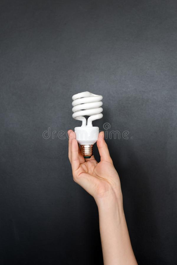 Recycling, electricity, environment and ecology concept - close up of hand holding energy saving lightbulb or lamp. Compact fluore stock photo