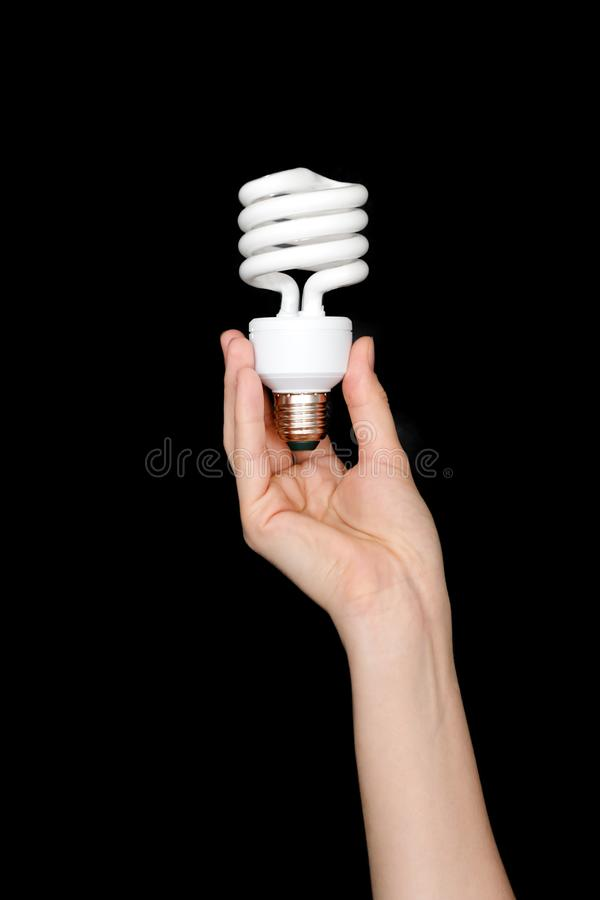 Recycling, electricity, environment and ecology concept - close up of hand holding energy saving lightbulb or lamp. Compact fluore stock images