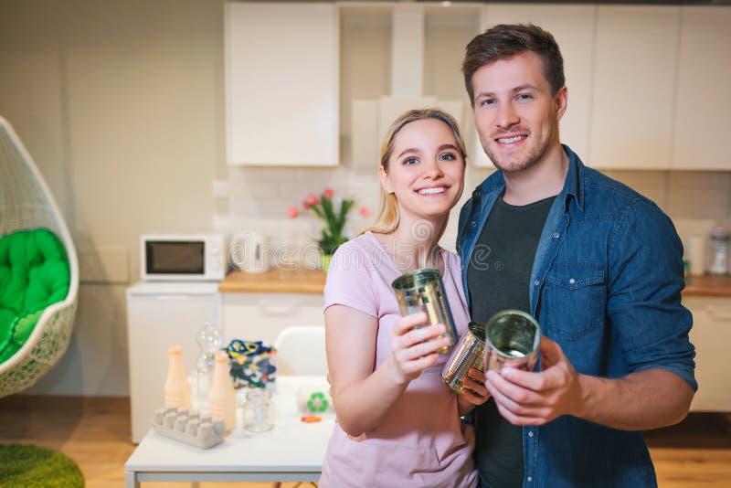 recycling Família de sorriso nova que guarda latas de lata do metal para a reutilização no fundo da cozinha imagens de stock royalty free