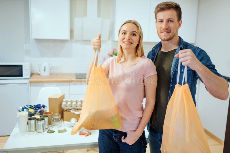 recycling Família de sorriso nova responsável que guarda sacos de lixo quando estar perto da tabela se encheu com o desperdício e imagem de stock royalty free