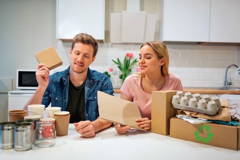 recycling Família nova que classifica o papel quando se sentar na tabela se encheu com o lixo na cozinha imagens de stock